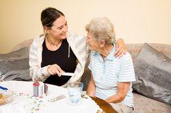 Woman giving elderly woman medicine